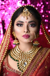 Portrait of beautiful Indian girl. Young female model with kundan jewelry set and Traditional Indian costume lehenga choli or sari.