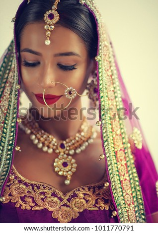 Portrait of beautiful indian girl. Young hindu woman model with kundan jewelry set. Traditional India costume lehenga choli or sari #1011770791