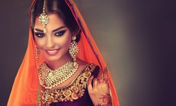 Portrait of beautiful indian girl. Young hindu woman model with tatoo mehndi  and kundan jewelry. Traditional Indian costume lehenga choli .