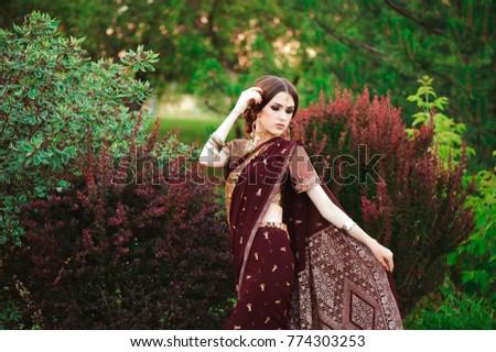 Portrait of beautiful indian girl. Young hindu woman model with tatoo mehndi and kundan jewelry. Traditional Indian costume saree. #774303253