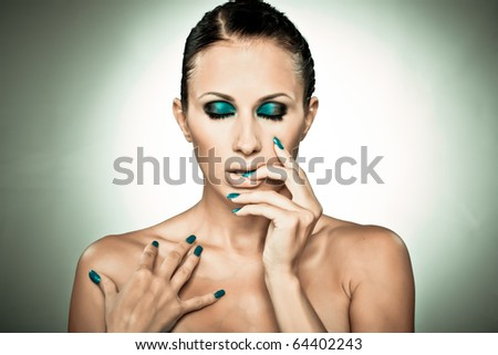 Portrait of beautiful lady showing blue nails isolated on grey in cross-process toning