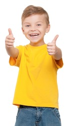Portrait of beautiful little boy giving you thumbs up over white background