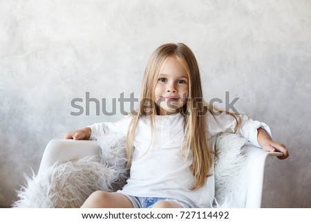 Portrait of beautiful little child model with big blue eyes, long straight hair and charming smile sitting in white armchair, posing for picture during fashion photo shooting at grey studio wall