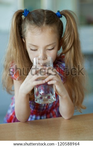Portrait of beautiful little girl close-up, which sits on table and drinking water from glass.