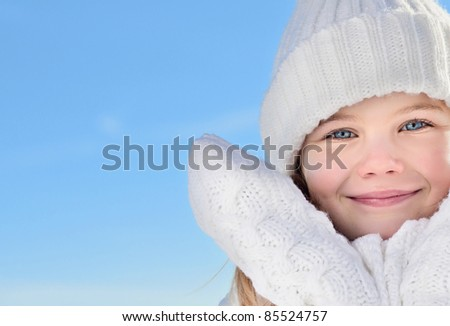portrait of beautiful little girl in warm clothing outdoors