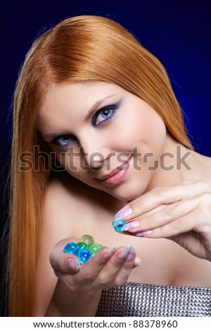 portrait of beautiful long-haired blue-eyed redhead girl posing with colorful glass balls in hands