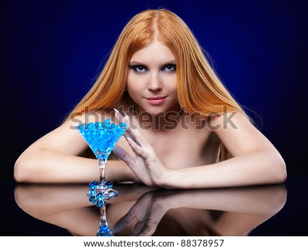...long-haired blue-eyed redhead girl with glass of fantasy cocktail.