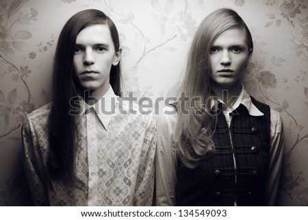 Portrait of beautiful long haired people in vintage style: handsome boy with black hair and gorgeous blonde girl posing together. Black and white (monochrome) studio shot.