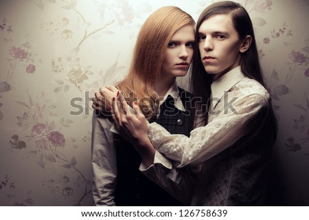 Portrait of beautiful long haired people in vintage style: handsome boy with brown hair and gorgeous red-haired girl posing together. Copy-space. Studio shot.