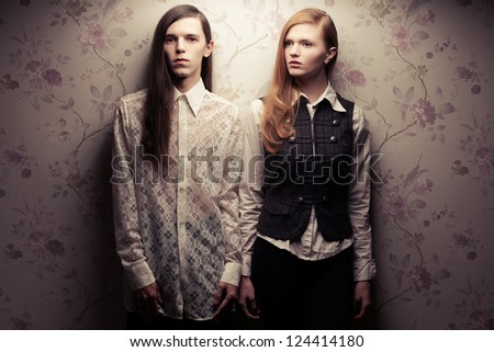 Portrait of beautiful long haired people looking like dolls in vintage style: handsome boy with brown hair and gorgeous red-haired girl posing together. Studio shot.
