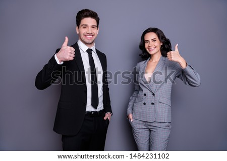Portrait of beautiful man and woman business people having brunet wavy curly hairstyle showing thumb up wearing black tux tuxedo suit isolated over grey background