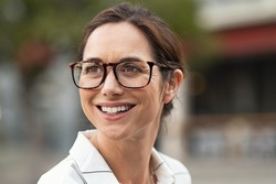 Portrait of beautiful mature woman looking away. Cheerful woman wearing eyeglasses and smiling. Close up face of happy carefree lady wearing eyeglasses on city street.