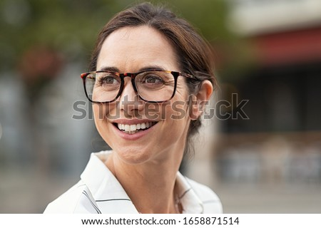 Portrait of beautiful mature woman looking away. Cheerful woman wearing eyeglasses and smiling. Close up face of happy carefree lady wearing eyeglasses on city street. Photo stock ©