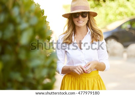 Portrait of beautiful mature woman walking on the street. Happy female wearing straw hat and sunglasses while on summer vacation. #477979180