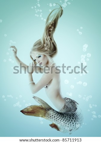 portrait of beautiful mermaid girl with fish tail and long blond hair swimming in ocean magic mythology being original photo compilation - stock photo