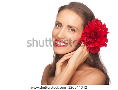 Portrait of beautiful middle aged woman with smooth healthy skin holding flower. Lady with red lipstick