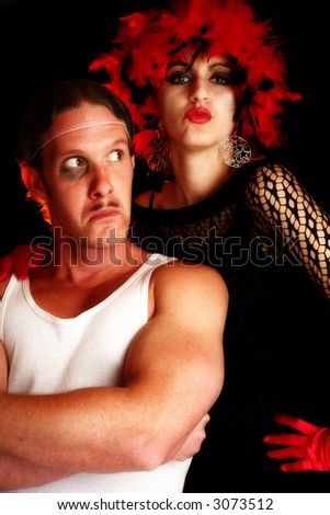 Portrait of beautiful Middle Eastern woman in costume with man dressed as thug.