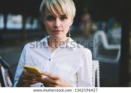 Portrait of beautiful millennial female blogger looking at camera during creating new publication with content text using application on modern mobile phone and wifi connection on publicity area