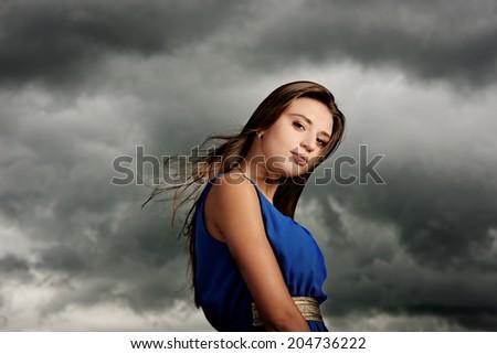 portrait of beautiful model on dark sky background. before storm
