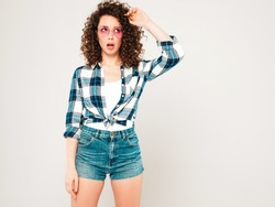 Portrait of beautiful  model with afro curls hairstyle dressed in summer hipster clothes.Sexy carefree girl posing in studio on gray background.Thinking about her problems