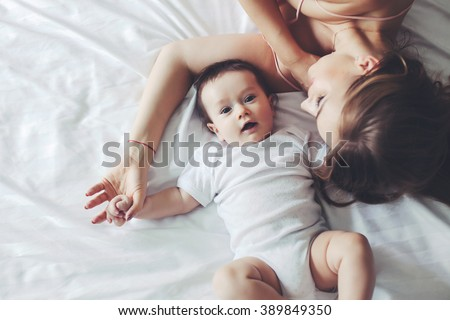 Portrait of beautiful mom playing with her 4 months old baby in bedroom, top view