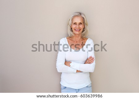 Portrait of beautiful older woman standing and smiling with arms crossed #603639986