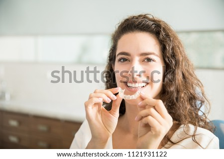 Portrait of beautiful patient holding orthodontic retainers in dental clinic