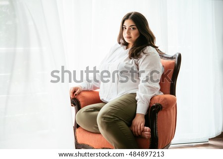 Portrait of beautiful plus size girl in white sitting in the armchair #484897213