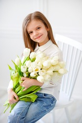 Portrait of beautiful pretty girl with white flowers tulips sitting on chair, smiling. Indoor photo.