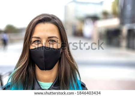 Portrait of beautiful real woman with mask for protection from Coronavirus, Covid-19. health, safety and pandemic concept - young woman wearing black face protective reusable barrier mask outdoors Foto stock ©