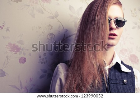 Portrait of beautiful red-haired fashion model in trendy sunglasses posing over vintage background. Studio shot