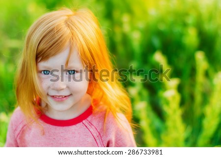 portrait of beautiful red-haired girl with big blue eyes and a sweet smile on background of green grass