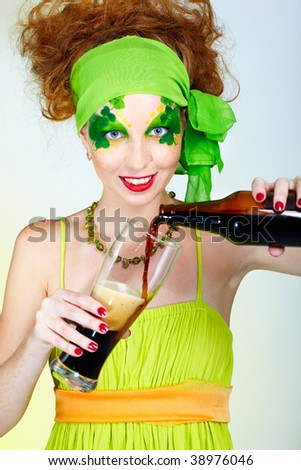 portrait of beautiful red-haired model with shamrock body art pouring glass with stout