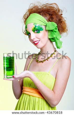 portrait of beautiful red-haired model with shamrock body art with the glass of green beer