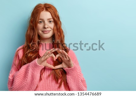 Portrait of beautiful red haired woman with freckled face, shows heart gesture over chest, wears oversized pink jumper, being passionate, express love to close person, stands over blue wall.