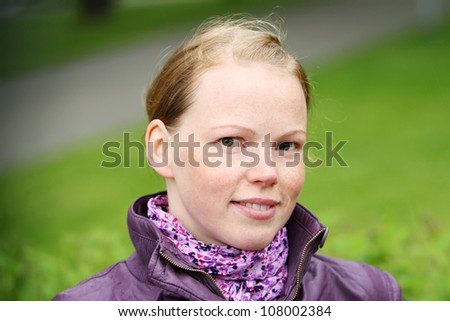 Portrait of beautiful redhaired girl  in the park