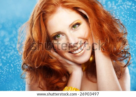 Portrait of beautiful redheaded girl on blue textured background