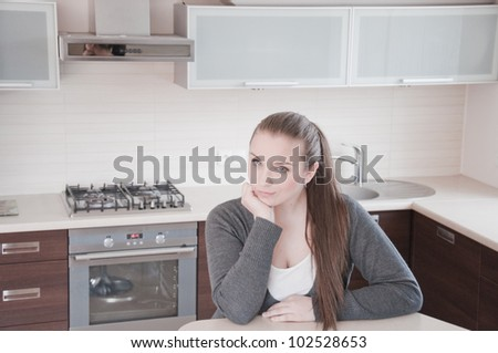 Portrait of beautiful relaxed young woman siting on the kitchen - Indoor