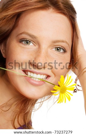 Portrait of beautiful rufous girl with yellow flower