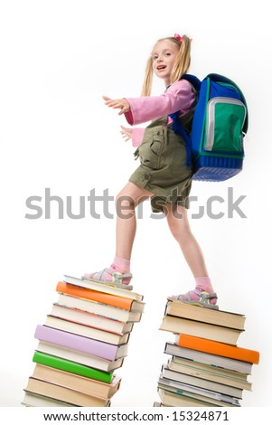 Portrait of beautiful schoolgirl standing on the top of books