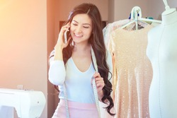 portrait of beautiful seamstress brunette with long hair talking on the phone . tailor creates a collection of outfits . young woman fashion designer dressmaker discusses outfit with customer by phone