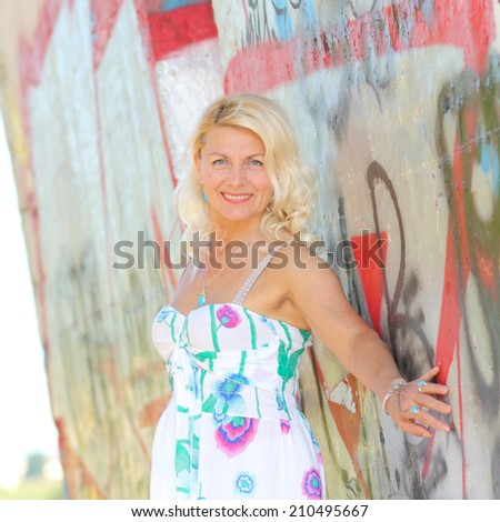 Portrait of beautiful senior blonde woman on the background of graffiti. Attractive senior lady portrait.