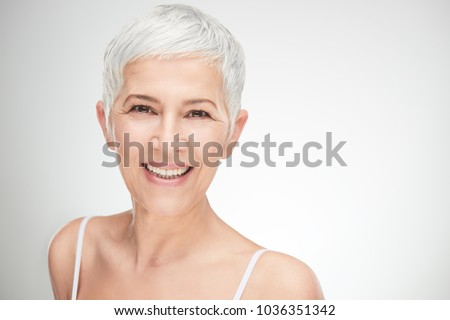 Photo of Portrait of beautiful senior woman in front of white background.