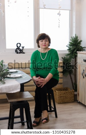 Portrait of beautiful senior woman in green pullover against kitchen interior background. Content woman smiling and looking at camera. Portrait of cheerful sixty-year-old grandmother.