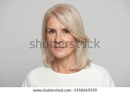 Portrait of beautiful senior woman looking at camera. Closeup face of mature woman face isolated over grey background. Aging aging concept.