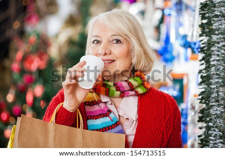 Portrait of beautiful senior woman with shopping bags drinking coffee at Christmas store