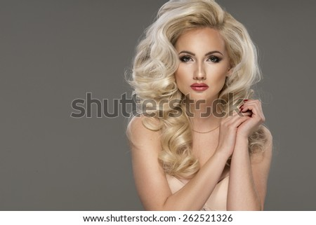 Portrait of beautiful sensual blonde woman with long curly hair. Beauty photo.