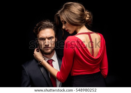Portrait of beautiful sensual couple in elegant clothes posing isolated on black #548980252