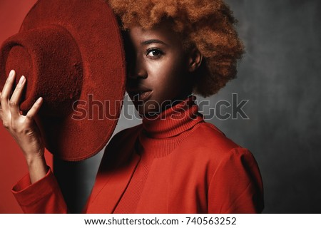 Portrait of beautiful sexy black female model wearing red sweater and jacket, holding red hat in her hand in studio with grey background #740563252