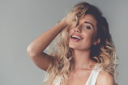 Portrait of beautiful sexy blonde girl touching her hair and smiling, on gray background